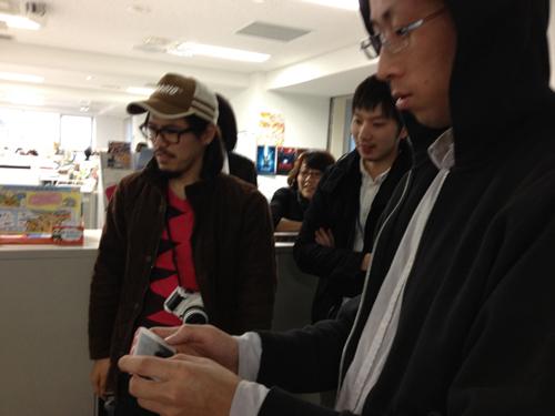 真剣な表情でiPhoneを見つめて操作するアートディレクターの青松くん